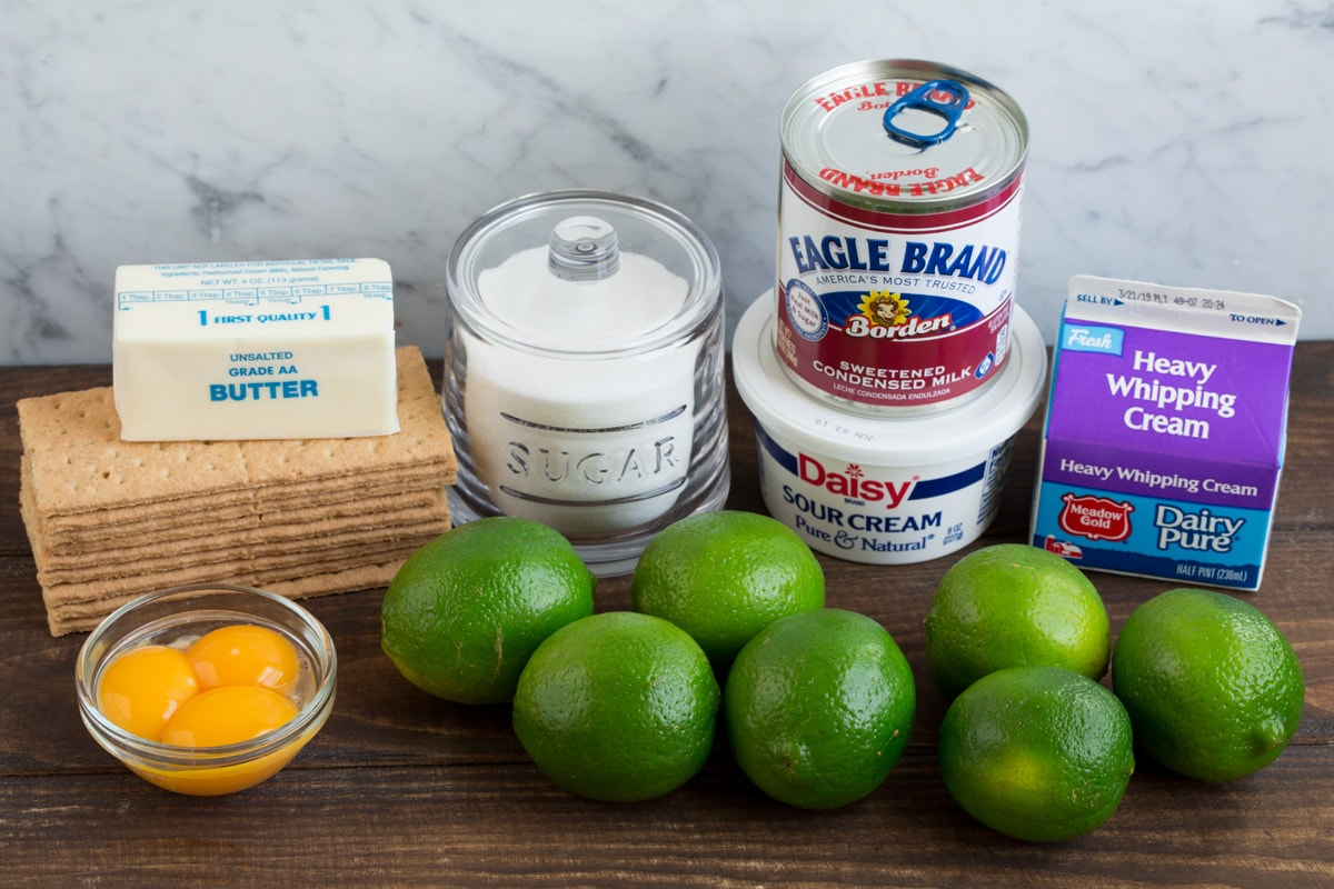 Eight ingredients needed for key lime pie shown here including graham crackers, butter, sugar, egg yolks, limes, sour cream, sweetened condensed milk and heavy cream.