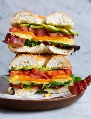 Bagel sandwich with microwave eggs, bacon, avocado, tomato, cheddar and lettuce. Sandwich is cut in half and stacked on a wooden plate set over a marble surface.