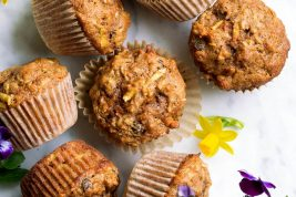 Overhead image of morning glory muffins on a marble surface decorated with spring flowers.