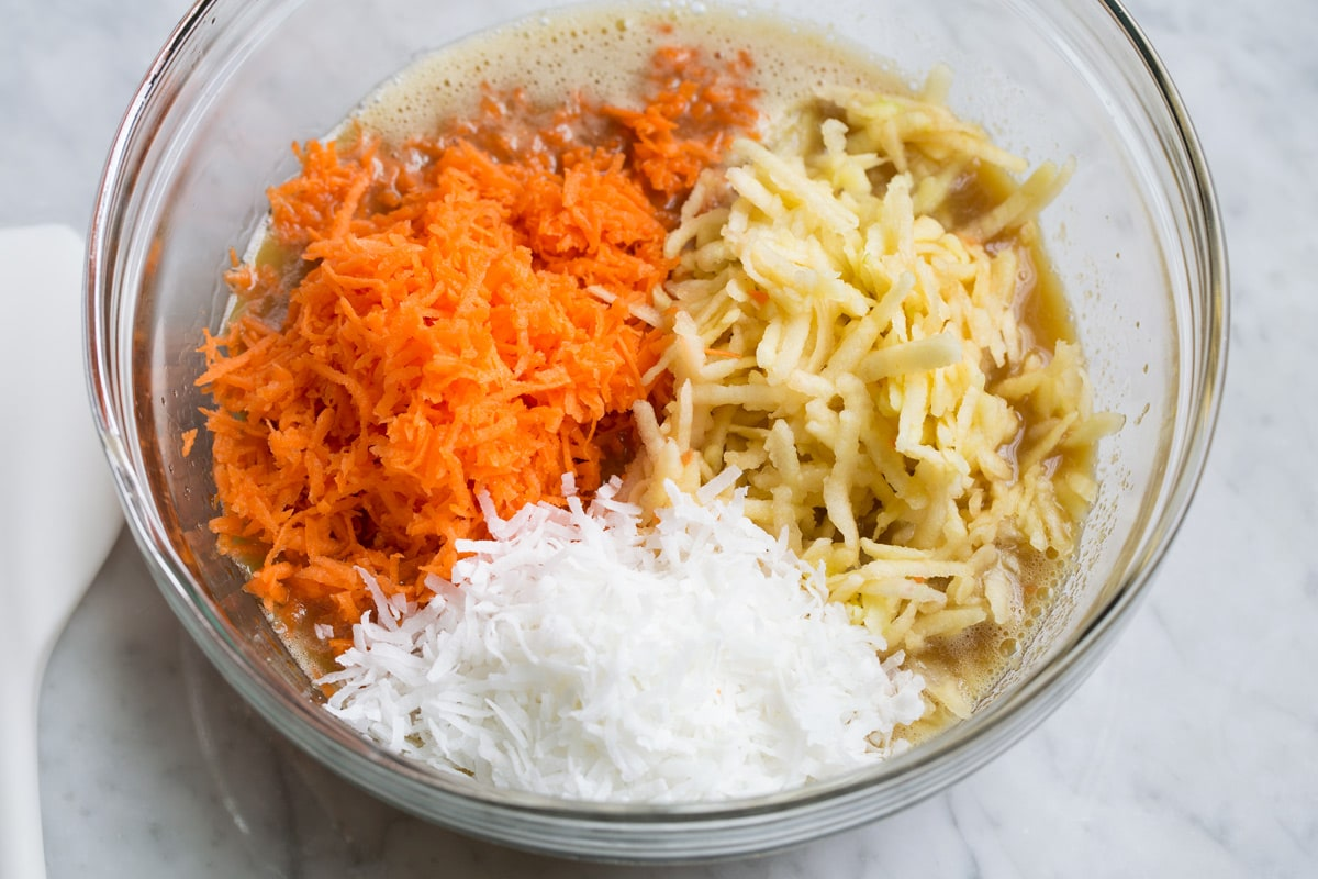 Adding shredded carrots, apples and coconut to morning glory muffin batter in glass mixing bowl.