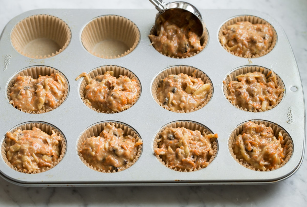 Scooping morning glory muffin batter into a paper lined muffin pan.