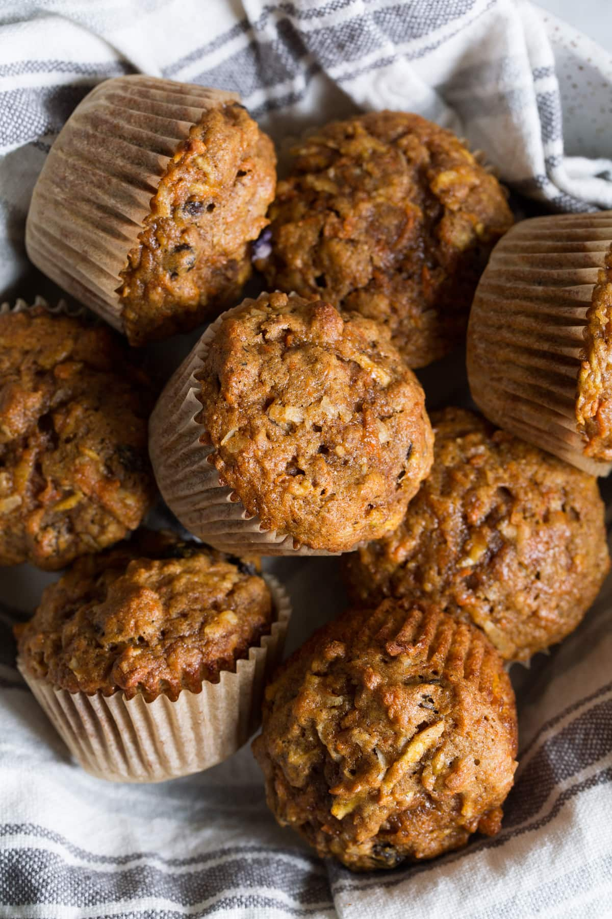 Morning glory muffins in a serving bowl with a kitchen towel.