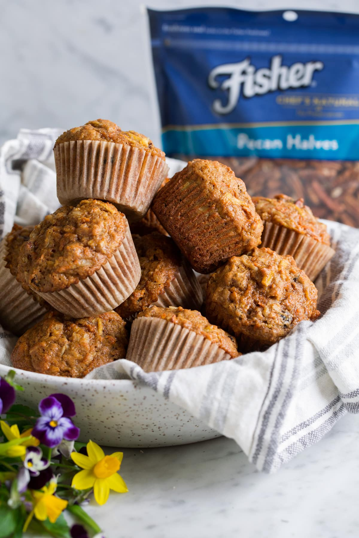 Morning glory muffins stacked in a speckled ceramic serving bowl