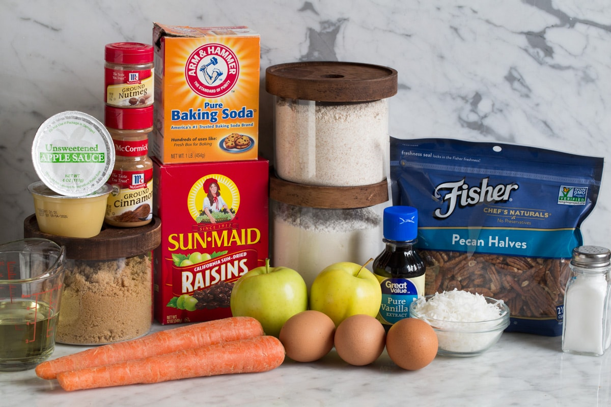 Ingredients needed for morning glory muffins shown here including wheat flour, white flour, baking soda, cinnamon, nutmeg, salt, brown sugar, apples carrots, raisins, coconut, eggs, vegetable oil, vanilla, pecans and applesauce.