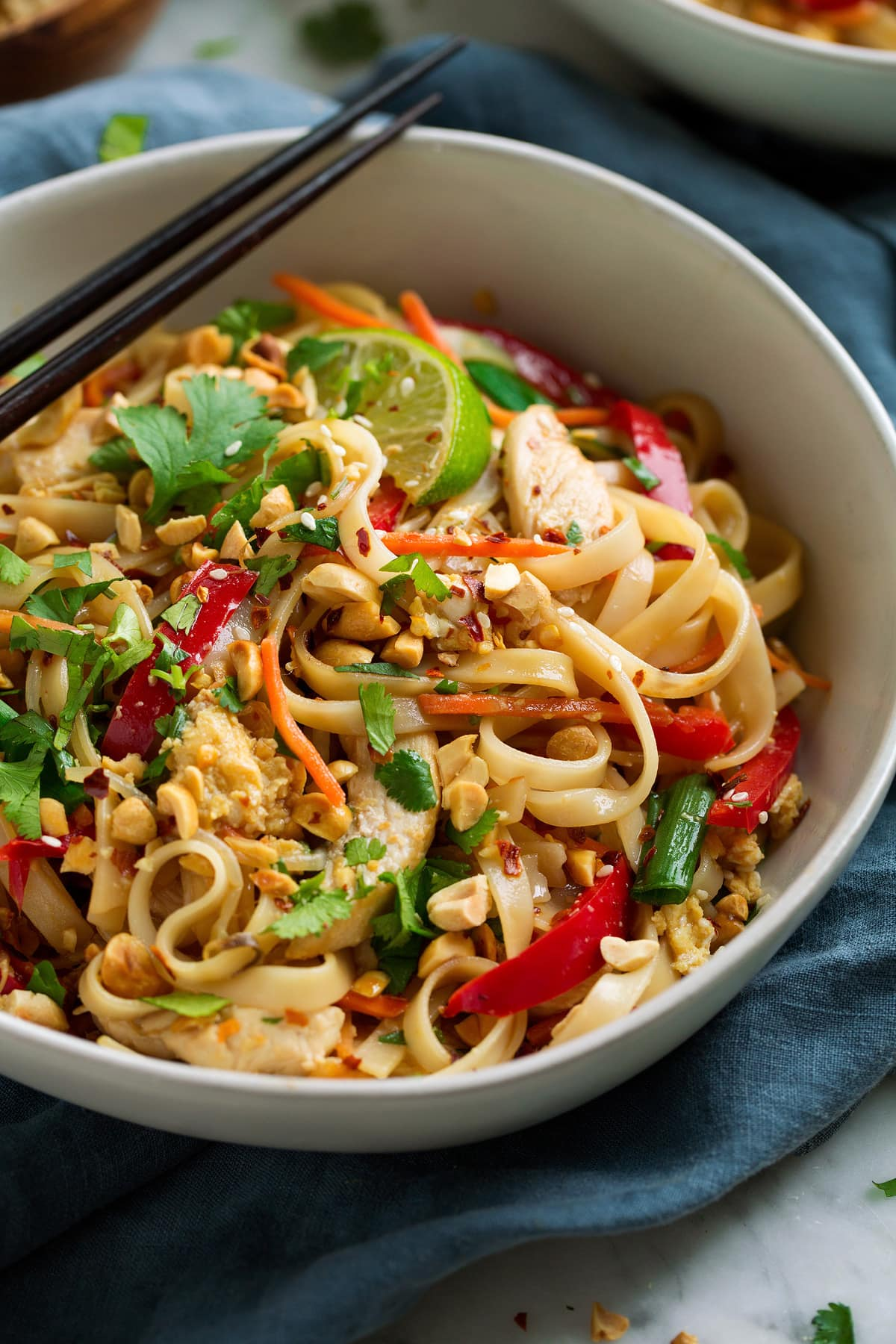 Close up image of Pad Thai showing rice noodles, vegetables, chicken, peanuts and cilantro.