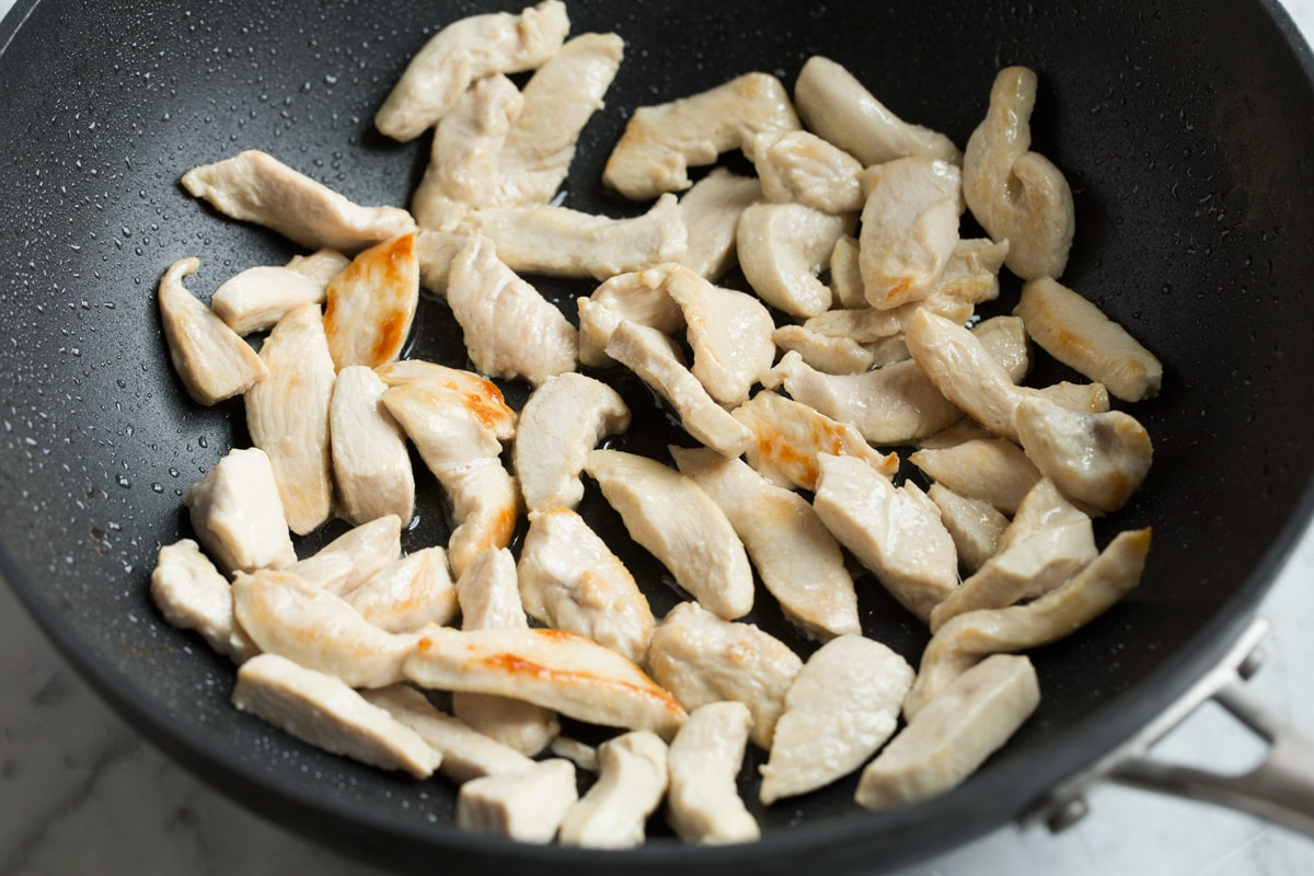 Showing how to make pad thai. Sautéing chicken breasts pieces in a wok.
