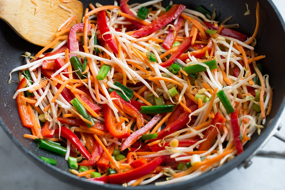 Sautéing vegetables in wok for pad thai.
