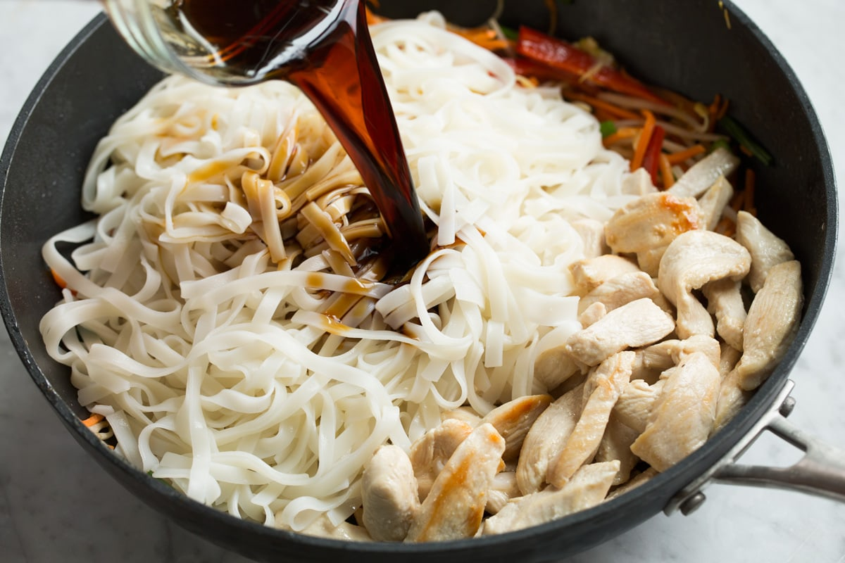 Adding rice noodles, cooked chicken and sauce to finish Pad Thai in wok.