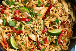 Pad Thai in a black wok with chicken and fresh vegetables.