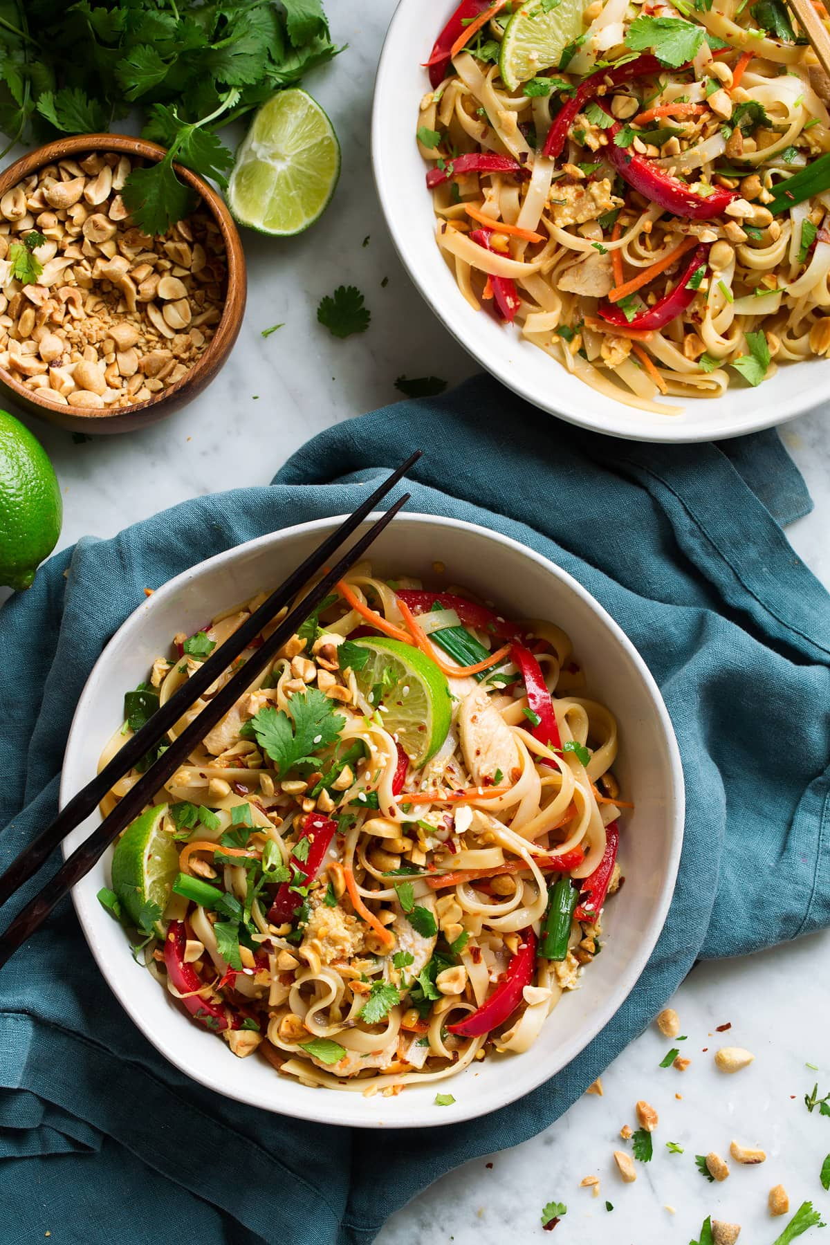 Two servings of pad thai in white bowls, with chopsticks on the side, set over a blue napkin.