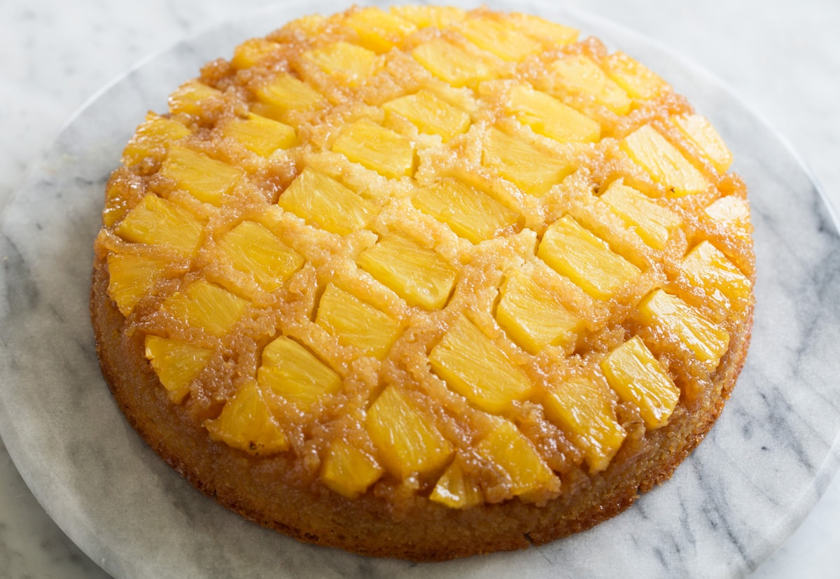 Whole Pineapple Upside Down Cake shown after baking and inverting onto marble platter.