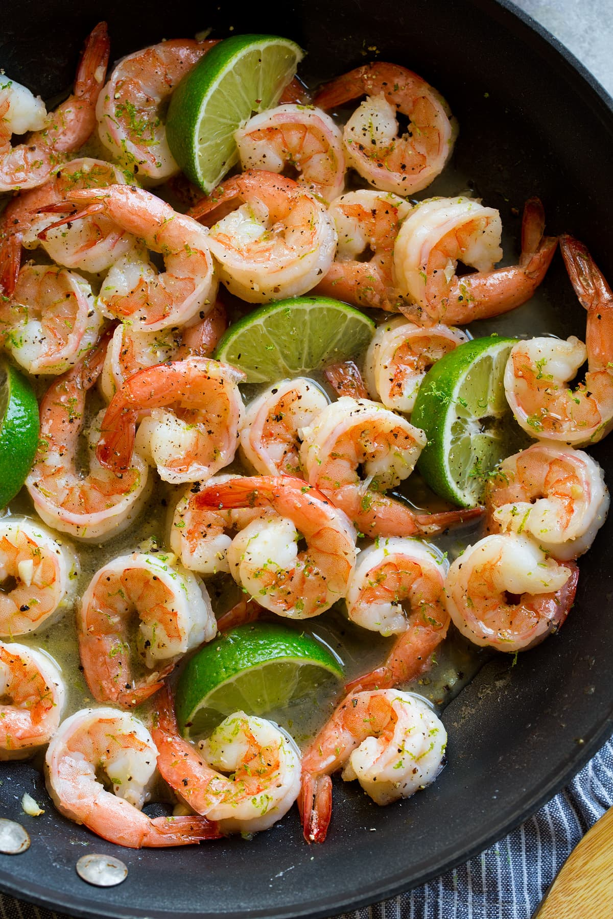 Shrimp with honey lime sauce in a black skillet.