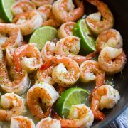 Close up image of shrimp with honey lime sauce in a black skillet.