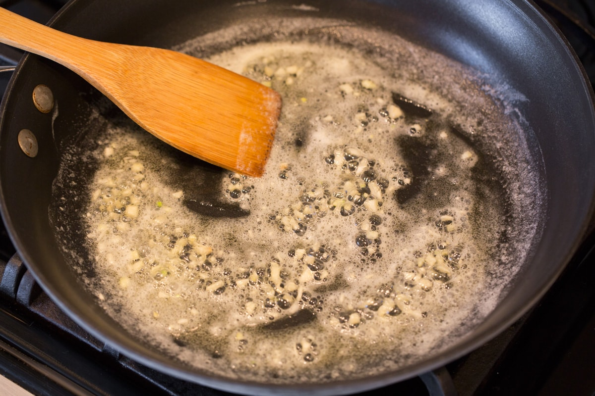 Melting butter and garlic in skillet.