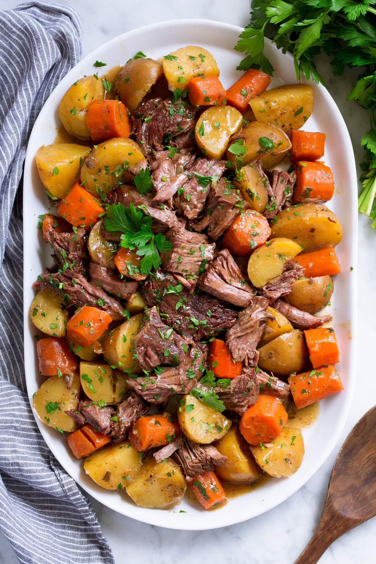 Slow Cooker Pot Roast with potatoes and carrots on a white oval serving platter set over marble.