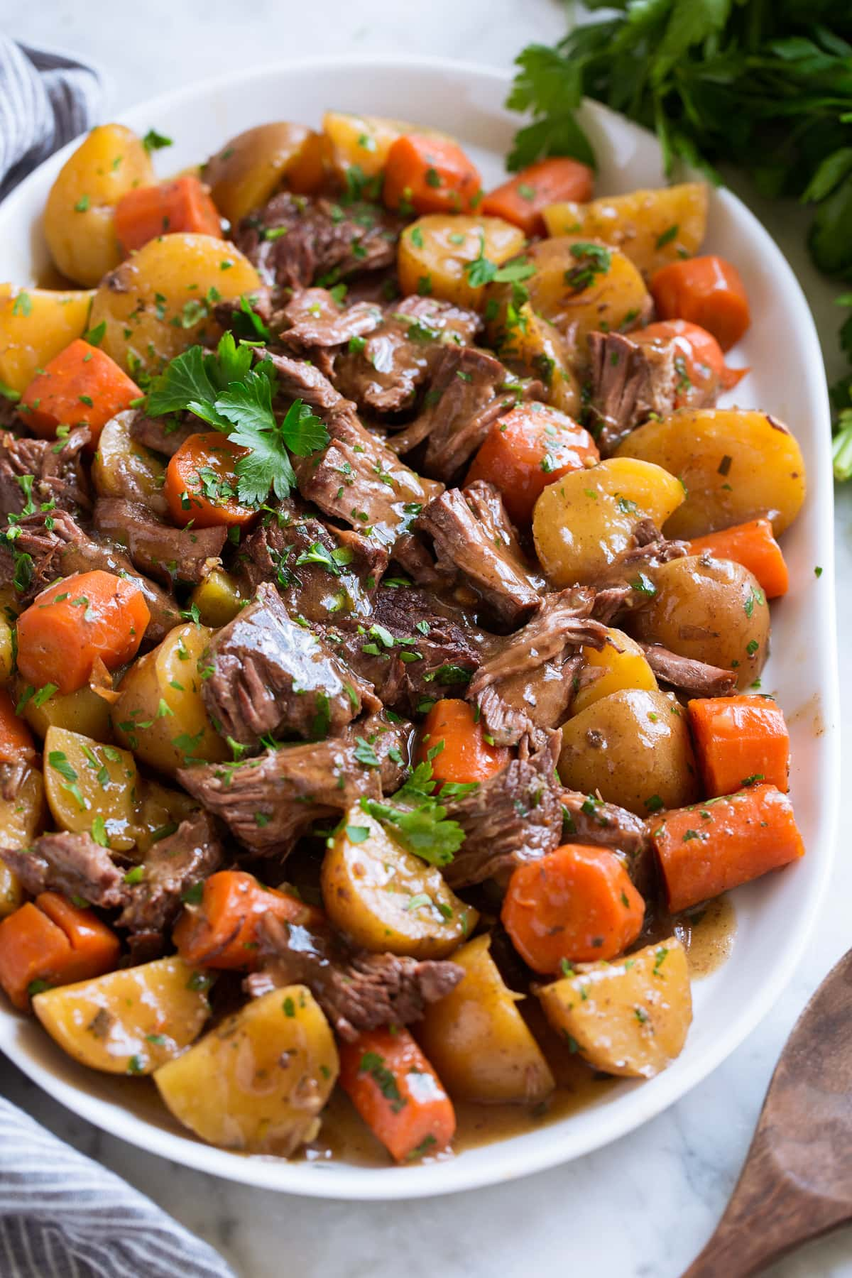Shredded slow cooker pot roast with potatoes and carrots on a white serving platter garnished with parsley.