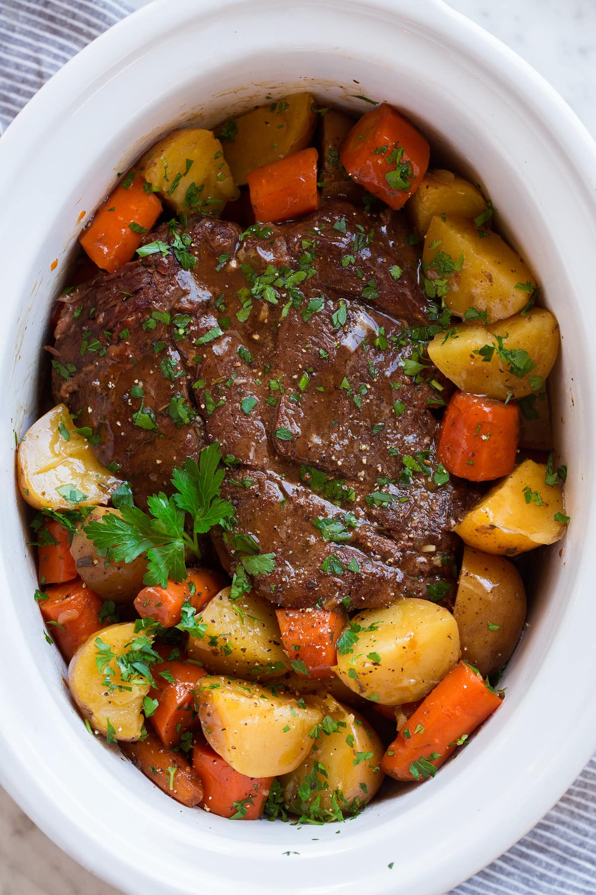 Slow cooker pot roast in a white crockpot