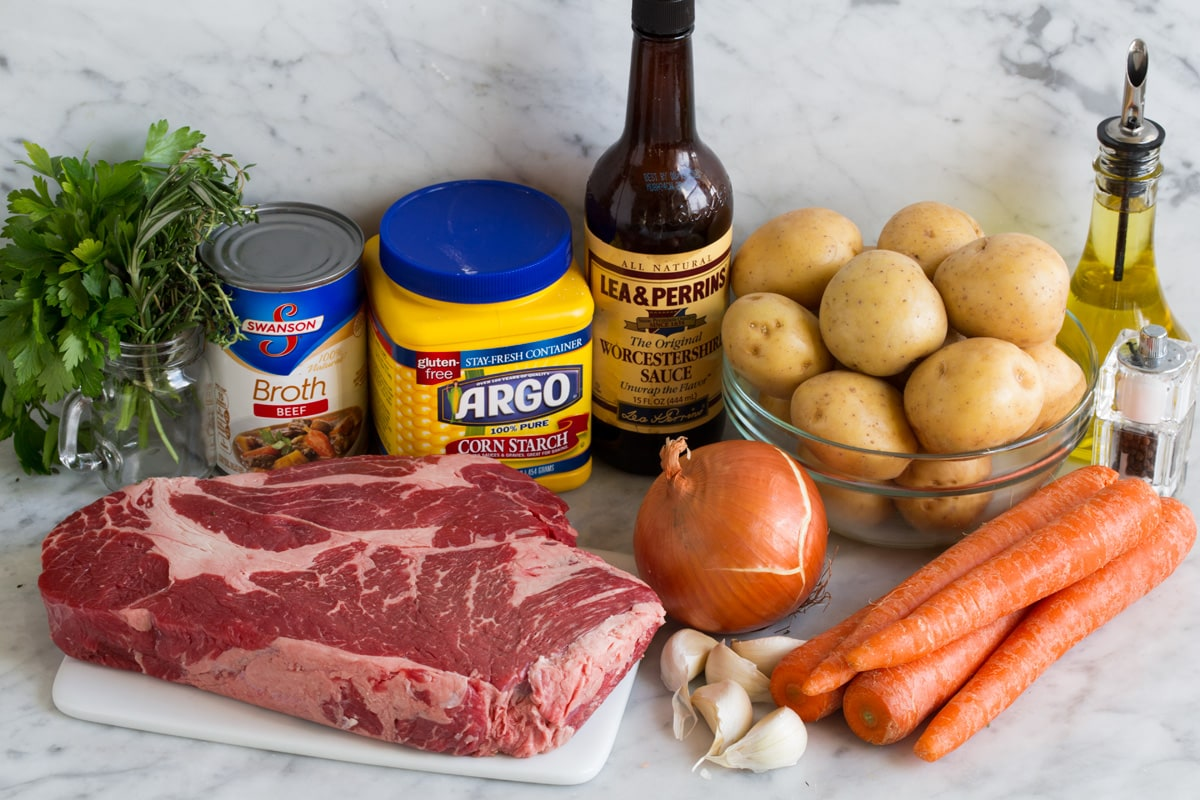 Ingredients needed for crockpot pot roast including chuck roast, yellow potatoes, carrots, onion, garlic, herbs, Worcestershire, beef broth, garlic, and cornstarch.