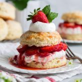 Strawberry shortcake on a white dessert plate. Made up of sweet buttermilk biscuit, macerated strawberries, and whipped cream. It is decorated on top with a fresh strawberry and mint leaves.
