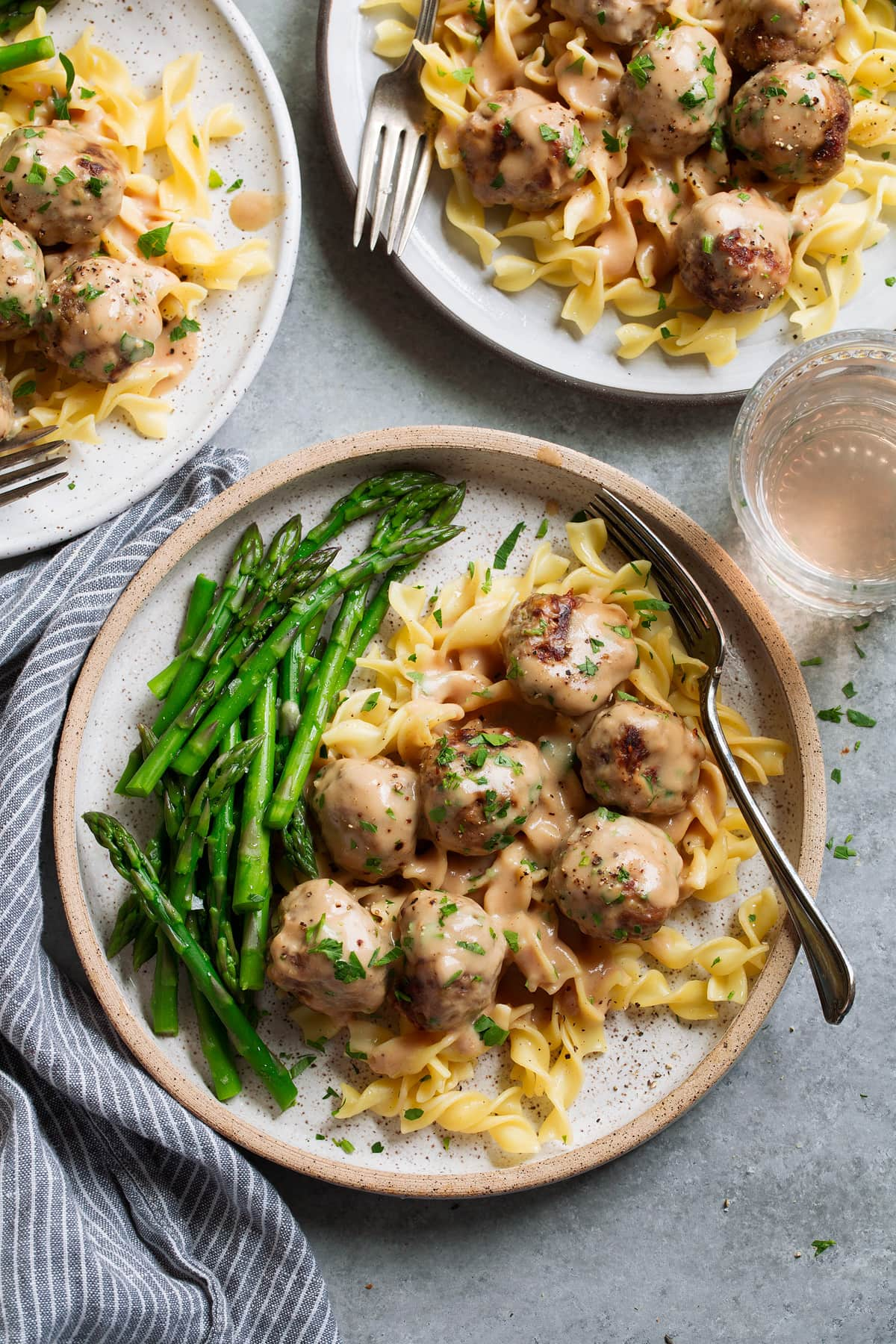 Three servings of Swedish meatballs on plates. Meatballs are laying over egg noodles and served with a side of steamed asparagus.