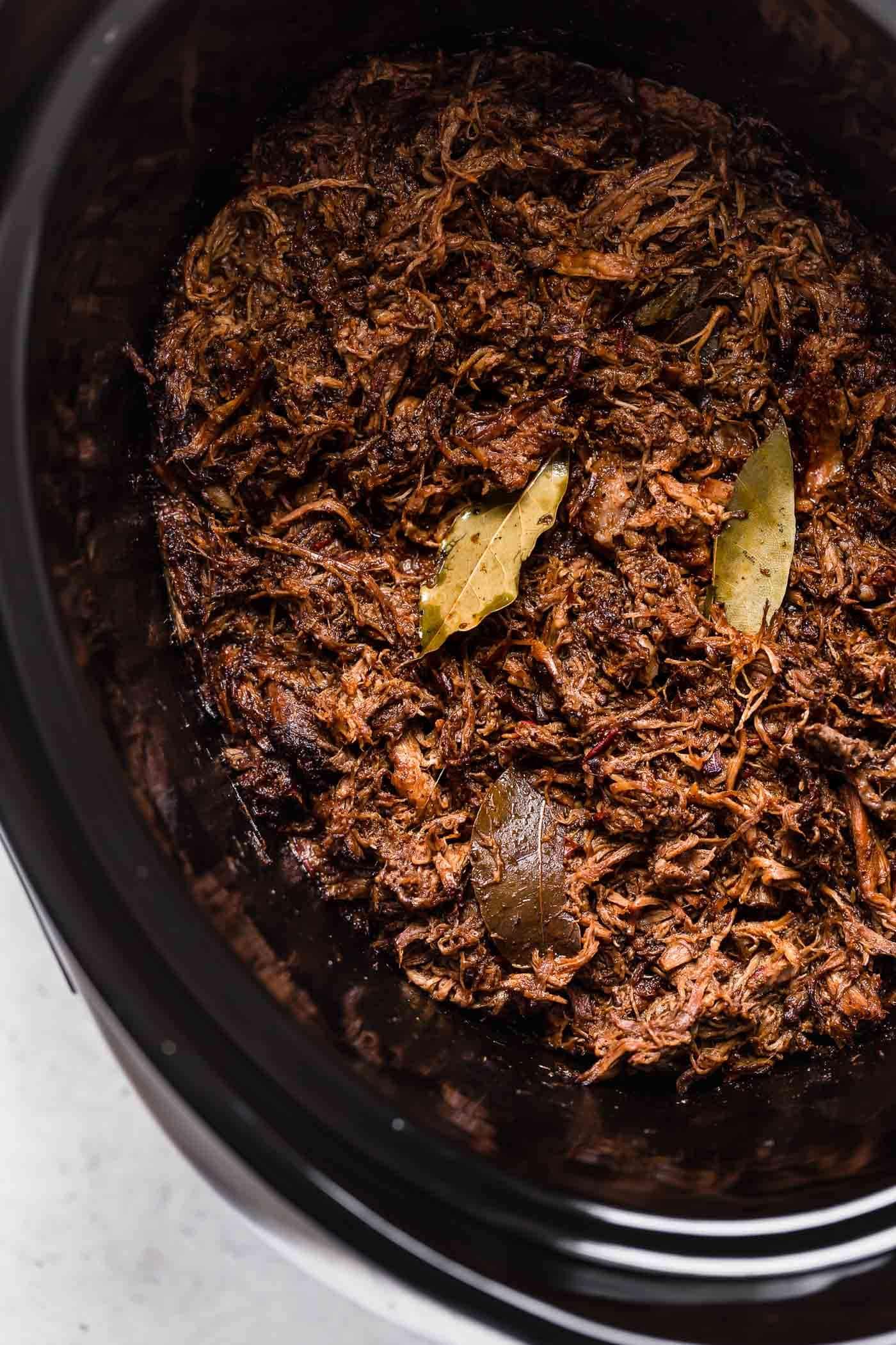 Shredded barbacoa beef in a crock pot.