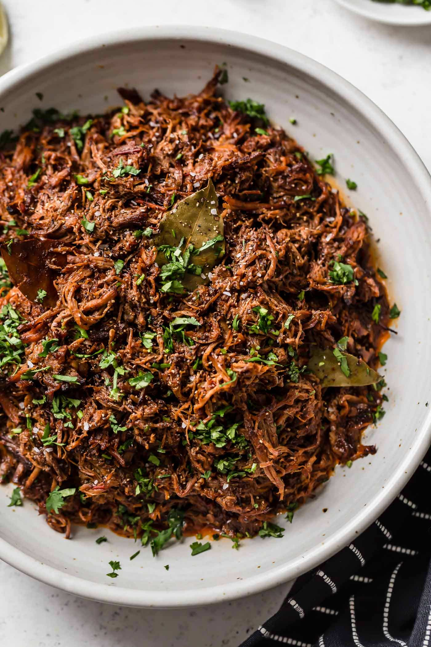 Slow cooker shredded barbacoa beef in a white serving bowl garnished with cilantro.