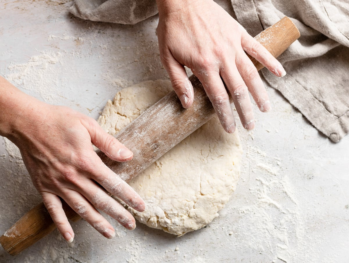 Gently rolling biscuit dough out using a rolling pin on a floured surface.