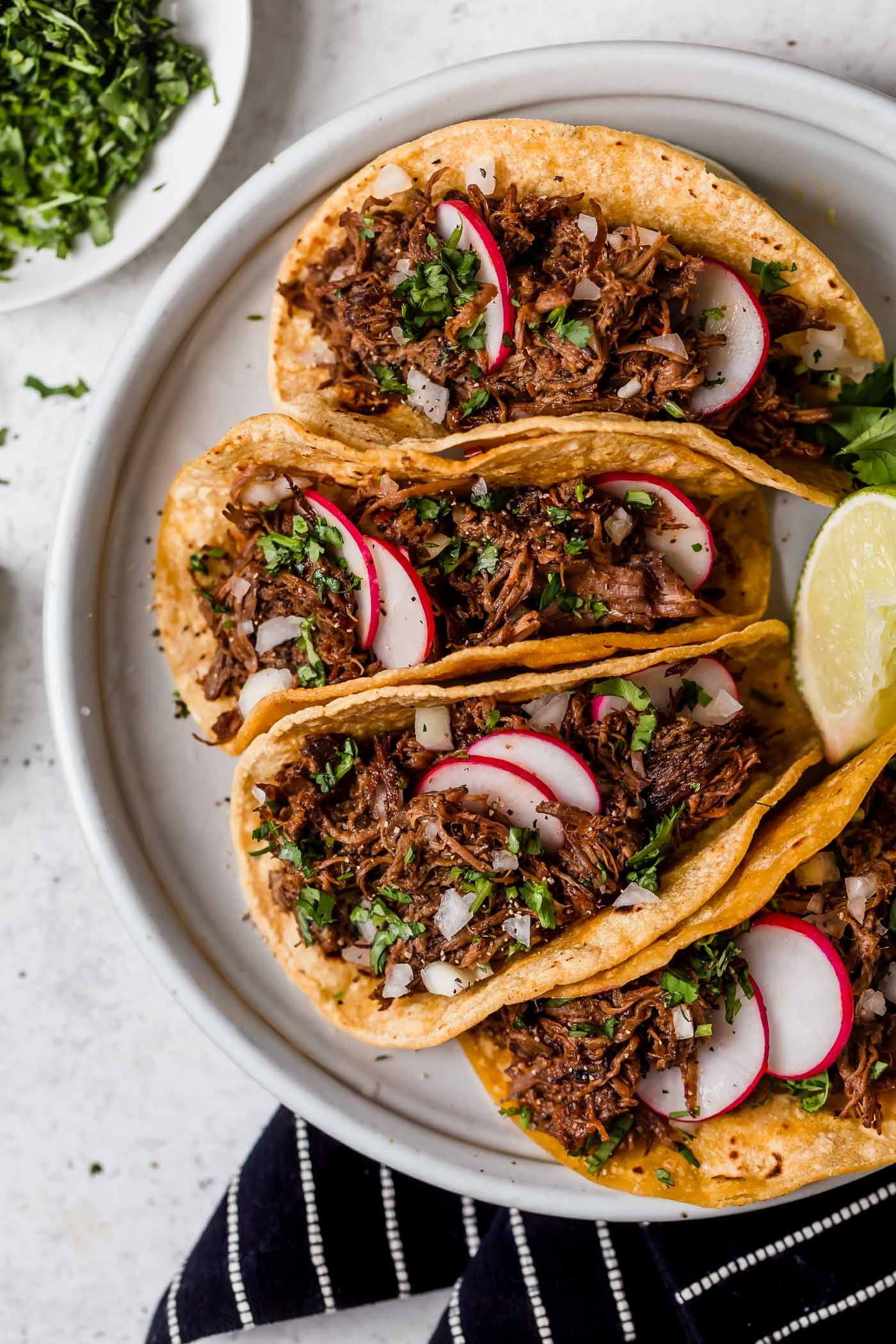 Barbacoa beef layered in corn tortillas to make tacos. Shown sitting on a light grey serving platter, beef is garnished with cilantro and radishes.