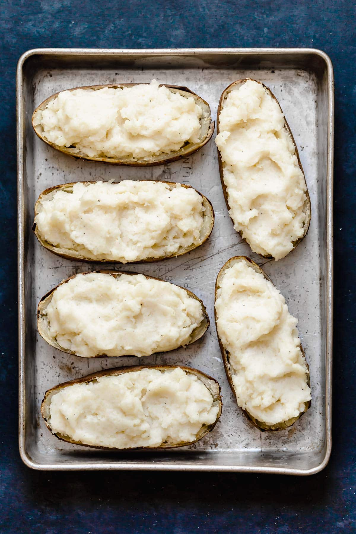 Six potato skins filled with mashed potatoes sitting on a metal baking dish.