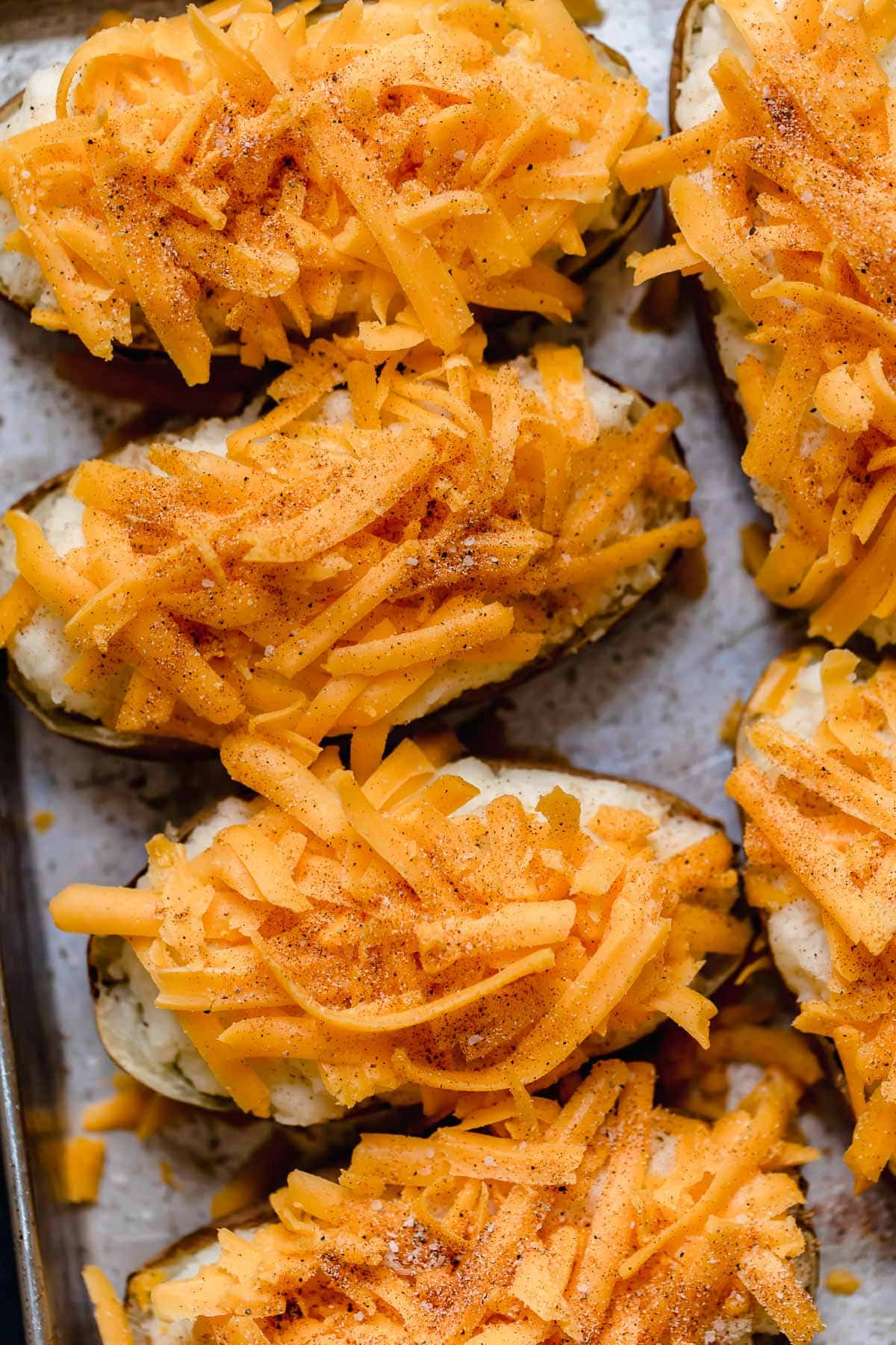 Twice baked potatoes filled with mashed potatoes and topped with shredded cheddar and seasoning. Shown before baking.
