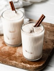 Horchata in two glass cups with ice cubes and a cinnamon stick. Cups are set over a wooden cutting board.