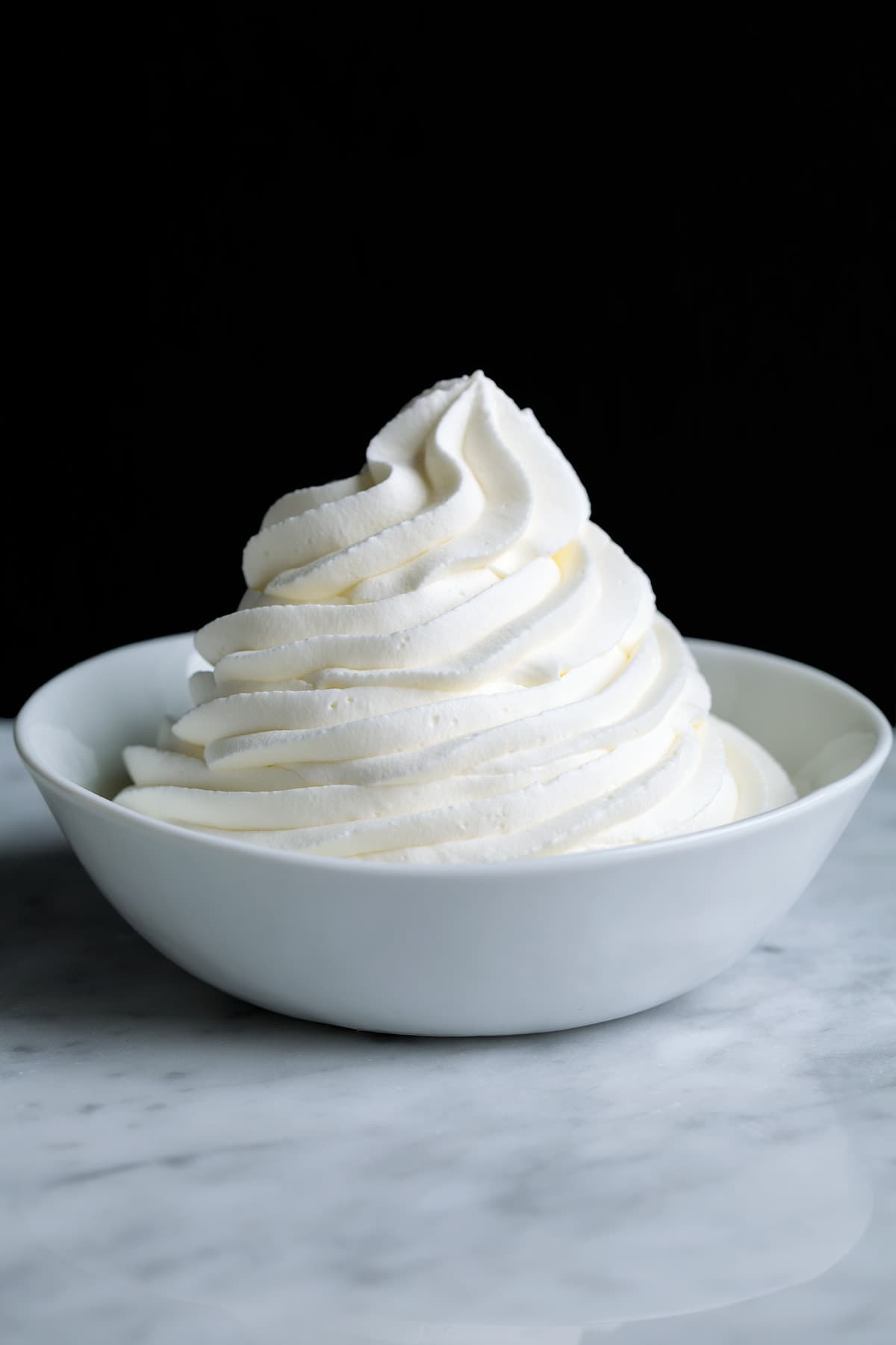 Piped mound of whipped cream in a white bowl set over a marble surface with a black background.