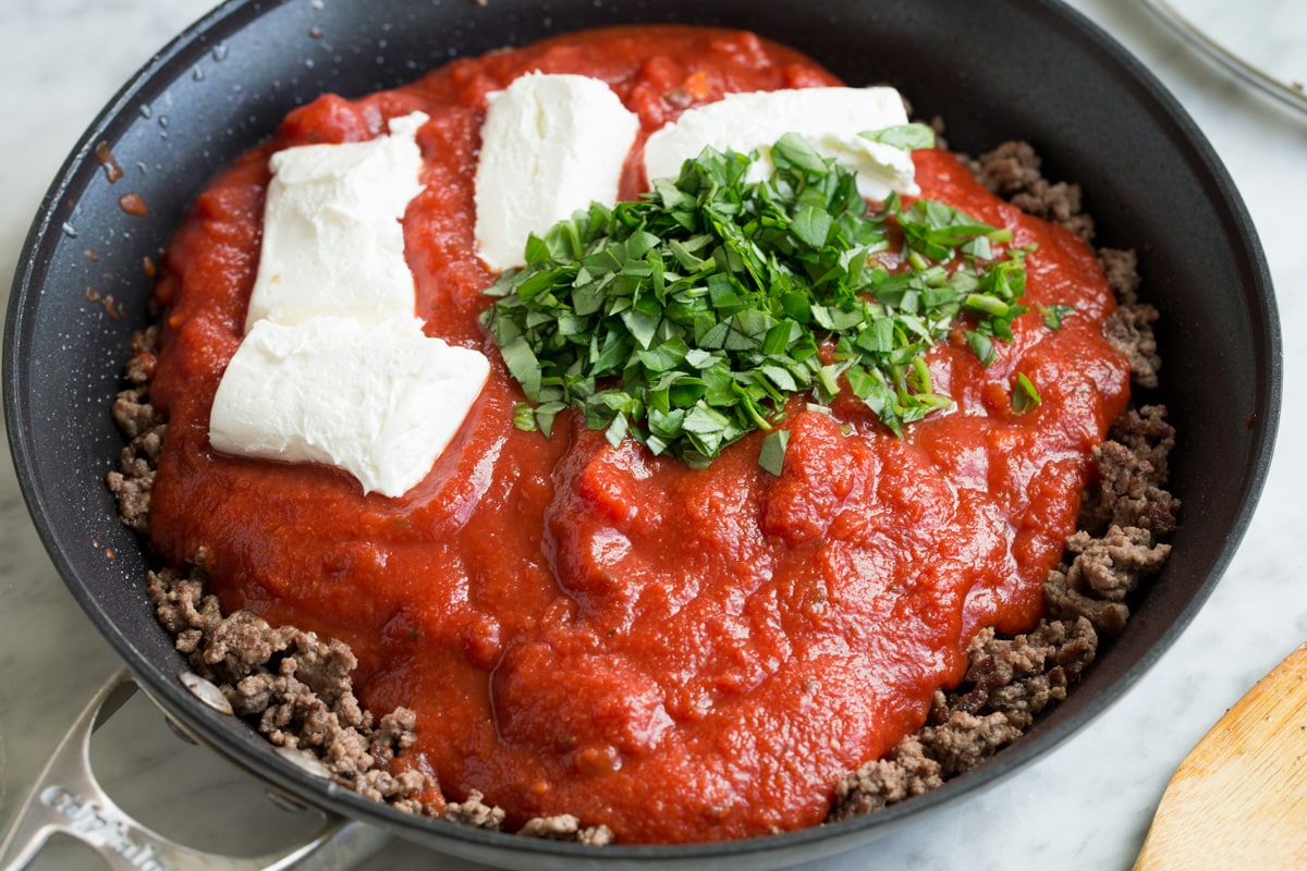 Adding marinara sauce, cream cheese and fresh basil to ground beef in skillet.