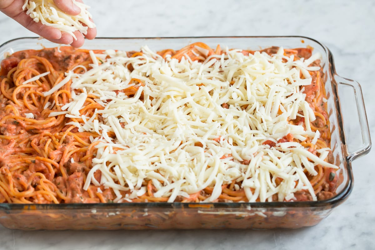 Adding cheese to baked spaghetti casserole.