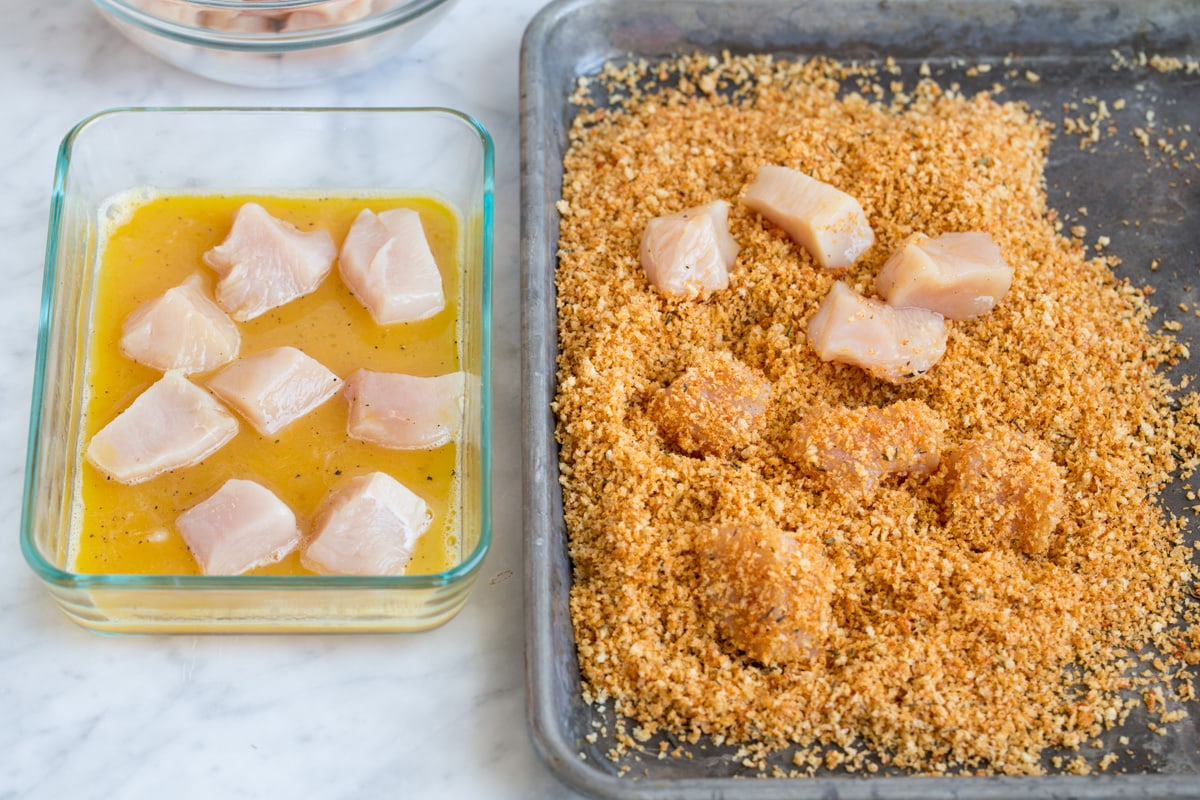 Showing how to make chicken nuggets. Tossing chicken pieces with egg then dressing in panko breadcrumb mixture on baking sheet.