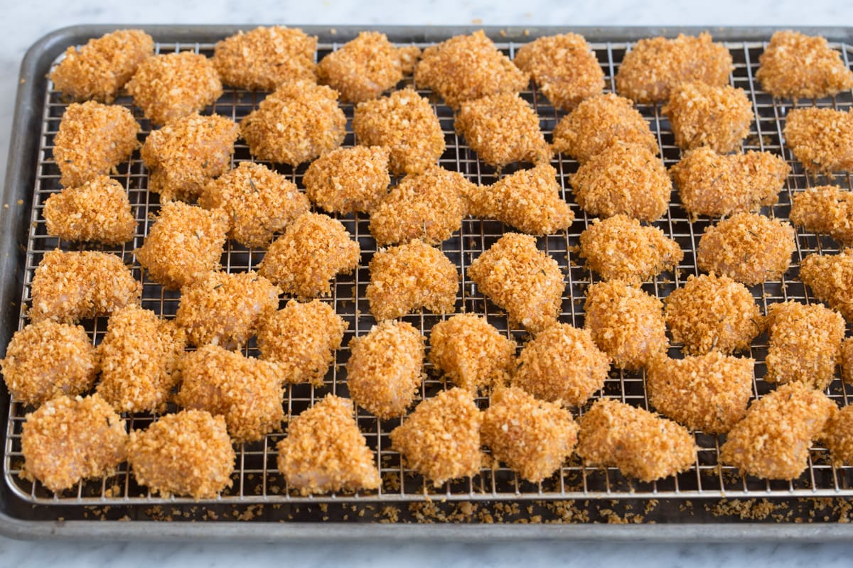 Showing how chicken nuggets look on wire rack over baking sheet before baking.