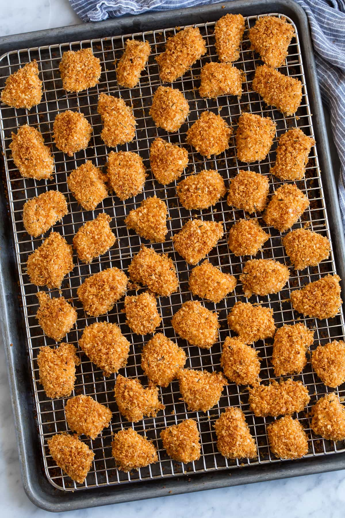 Chicken Nuggets shown on wire rack over baking sheet after baking.