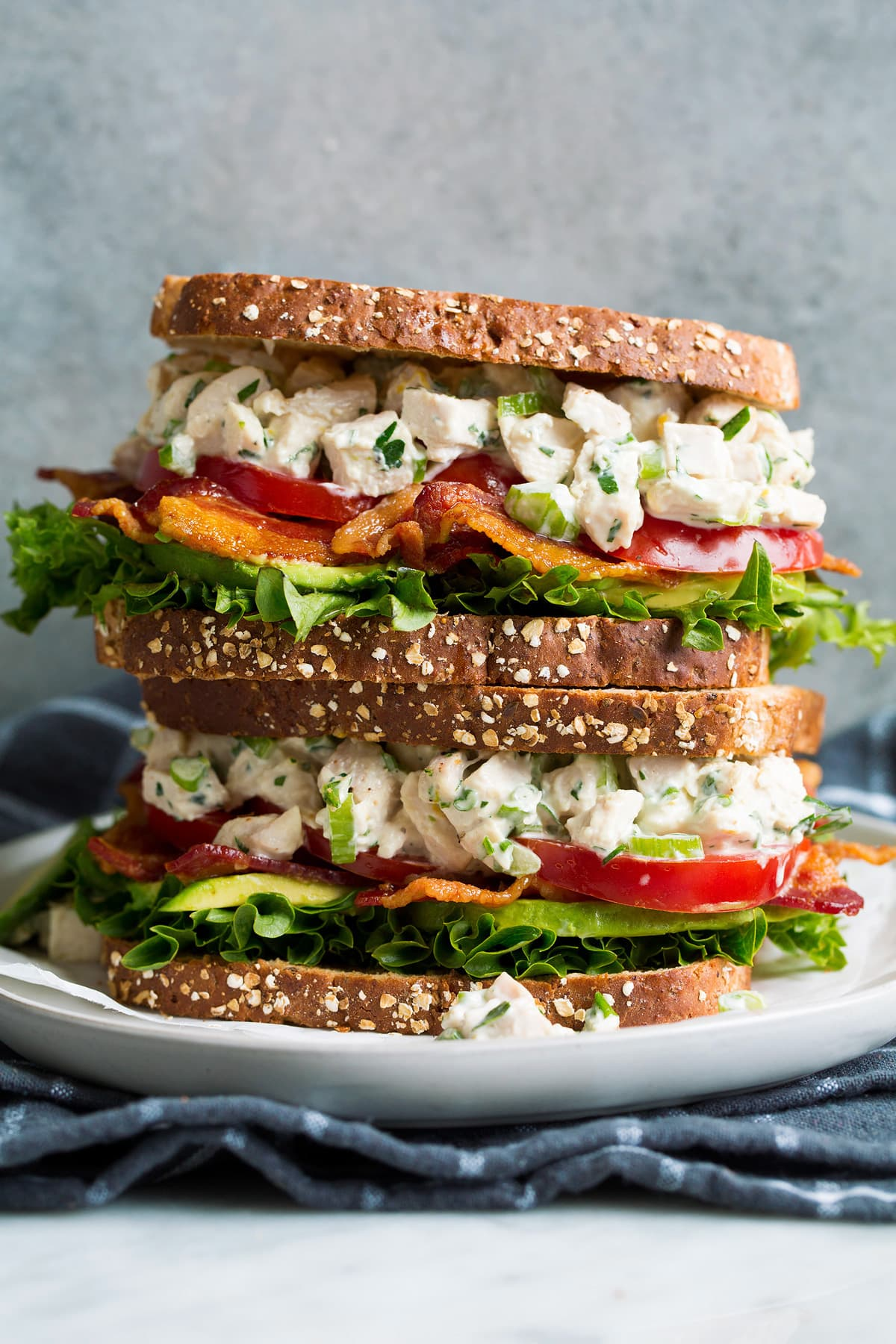 Stack of two chicken salad sandwiches on a white plate set over a dark grey cloth.