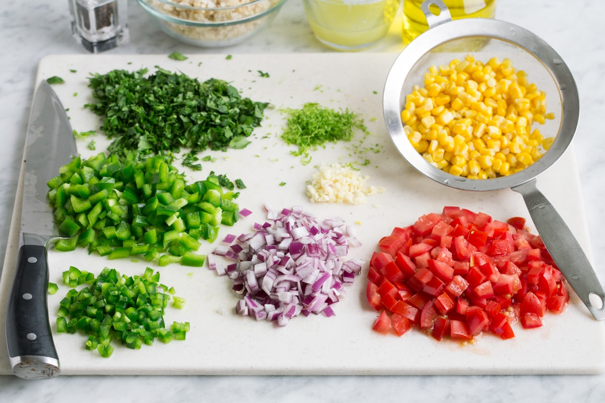 Chopped vegetables on a cutting board with corn in a colander to drain and rice in the background in a bowl.