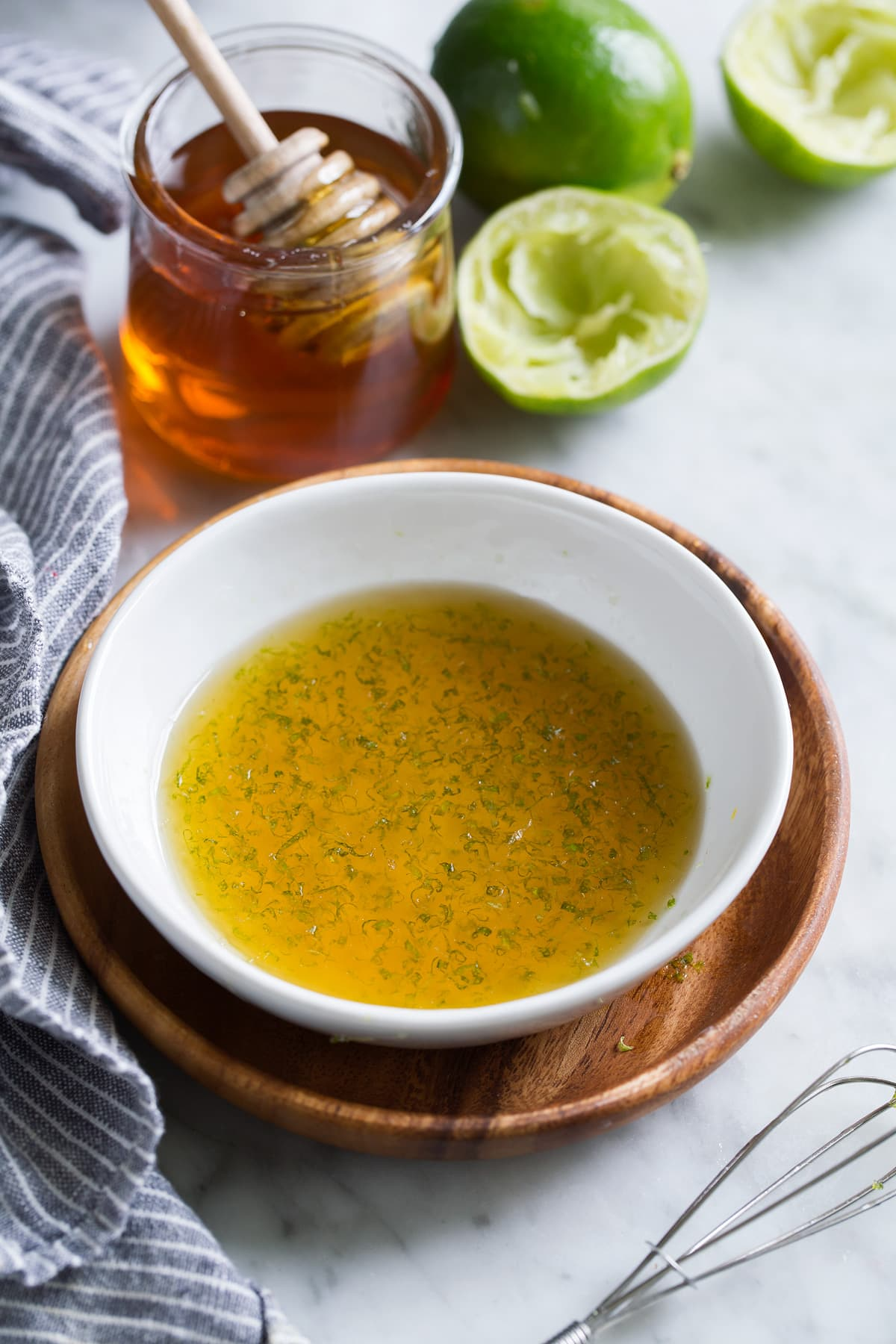 Honey lime fruit salad dressing in a small white bowl set over a wooden plate.
