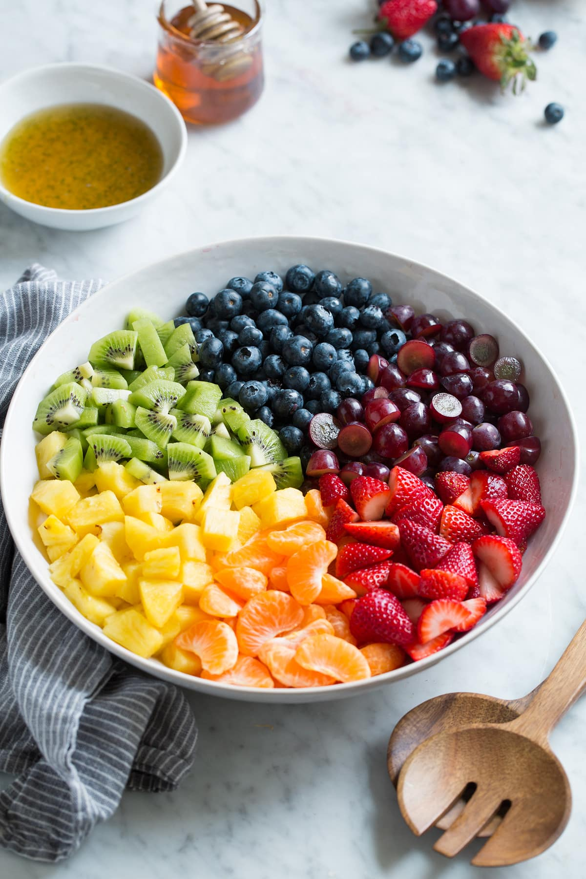 Fresh strawberries, mandarin oranges, pineapple, kiwi, blueberries, and grapes in sections in a large white serving bowl.