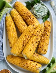 Eight grilled corn on the cob on a white oval platter with flavored butters on the side.