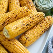 Close up image of stack of grilled corn on the cob on a white oval serving platter set over a marble surface.