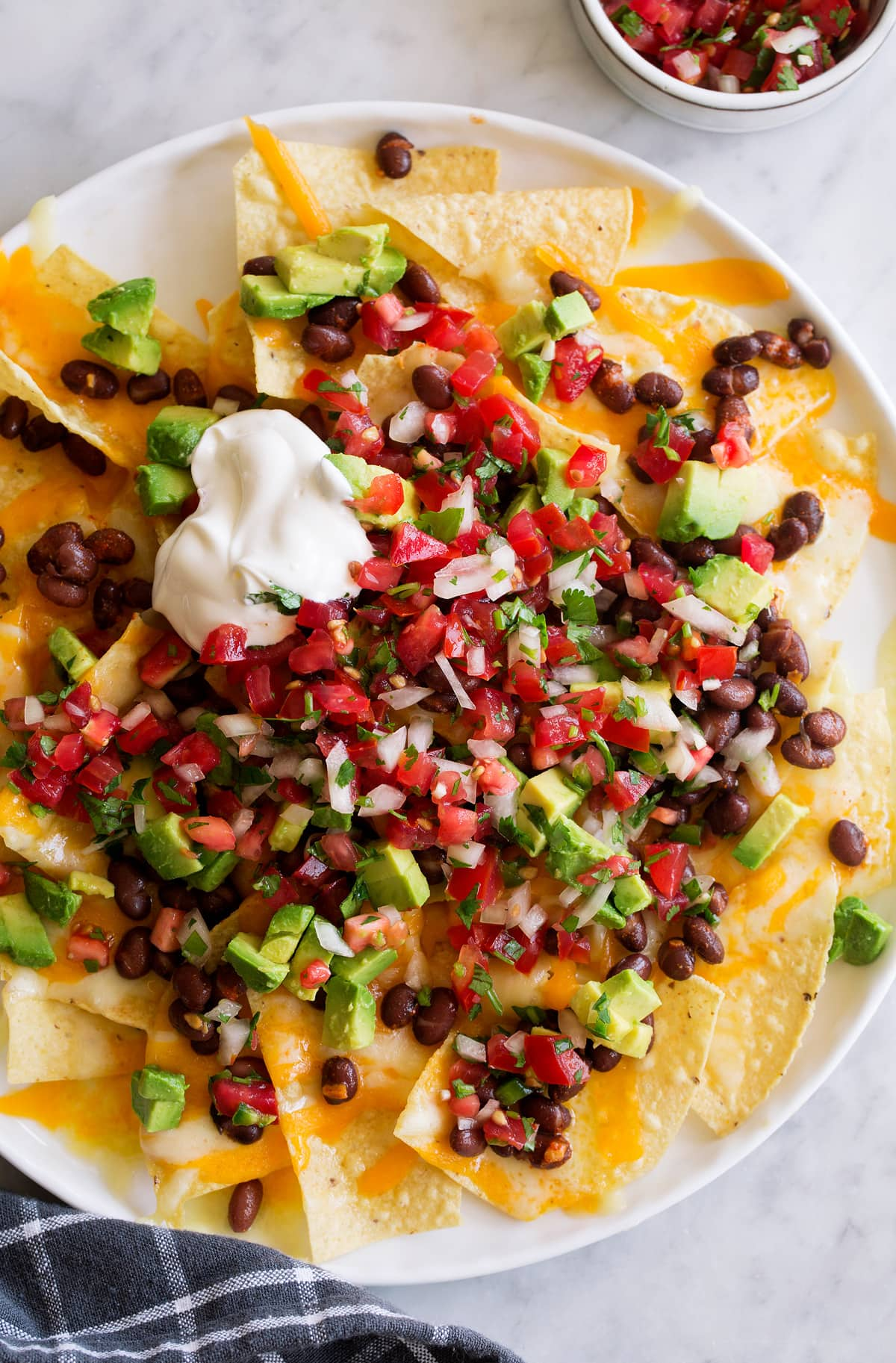 Pico de gallo over nachos along with melted cheddar, black beans, diced avocado and sour cream.
