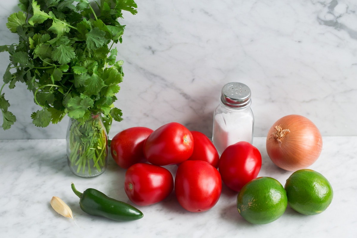 Pico de gallo ingredients: tomatoes, lime, yellow onion, jalapeno, garlic, salt and cilantro.