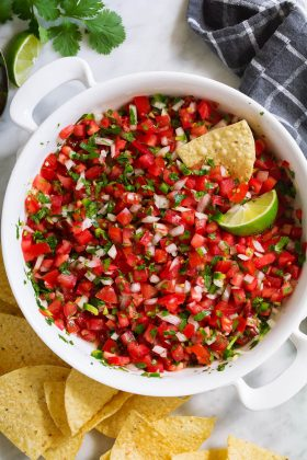 Overhead image of homemade pico de gallo in a white serving bowl with a side of tortilla chips.