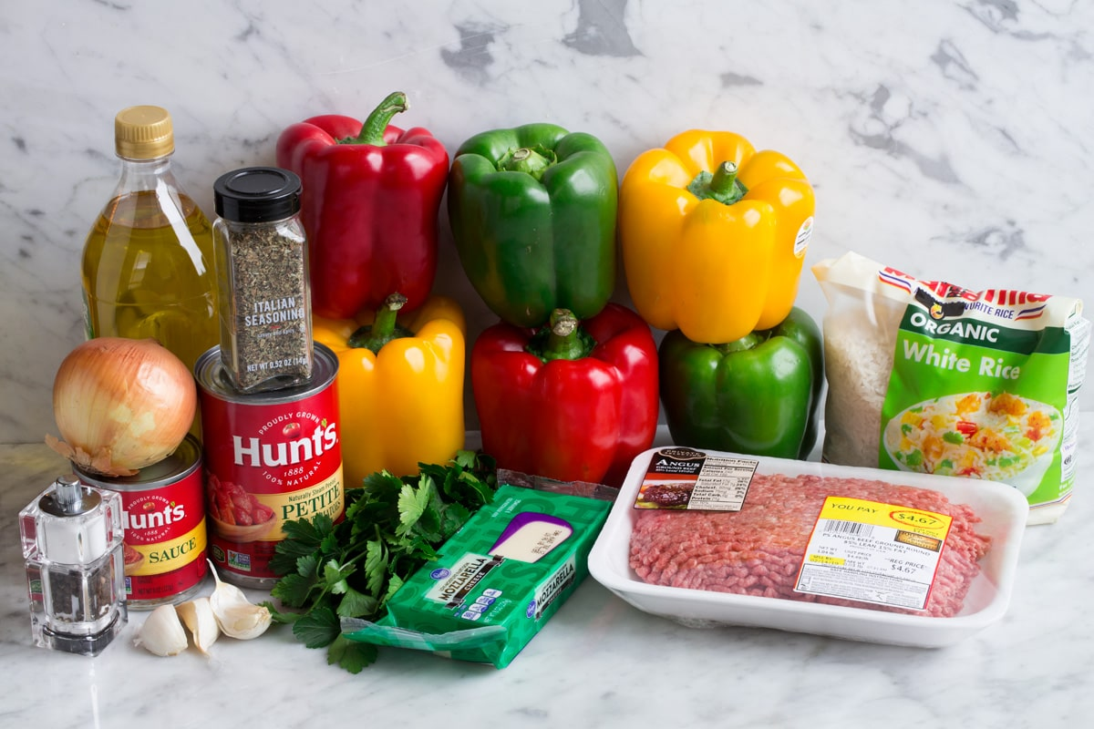 Ingredients to make stuffed peppers show here including bell peppers, ground beef, tomato sauce, diced tomatoes, garlic, onion, italian seasoning, mozzarella, white rice, olive oil, parsley.