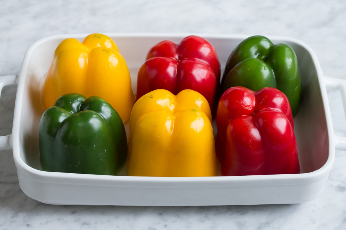 6 multicolor bell peppers in a white baking dish.