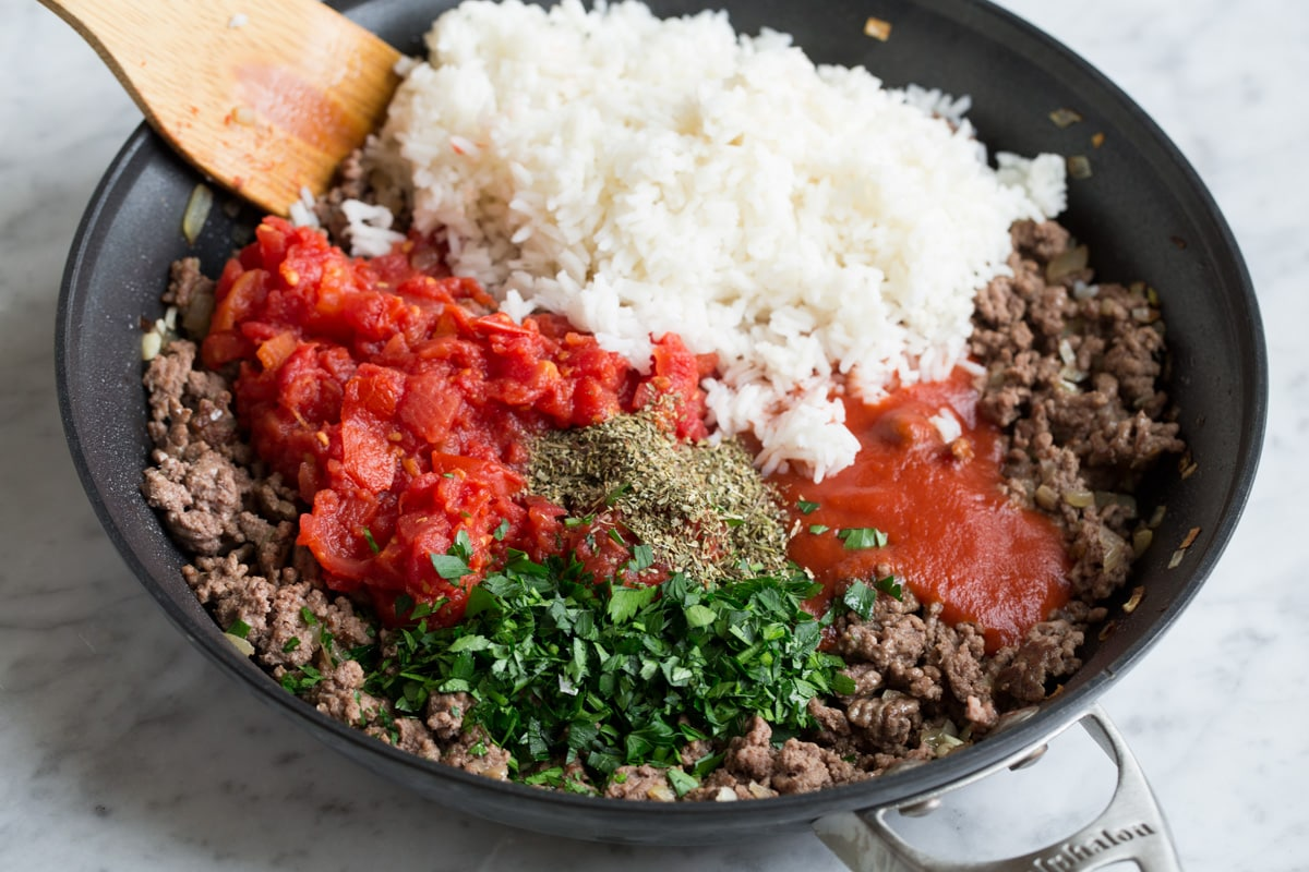 Adding cooked rice, tomatoes, tomato sauce, and herbs to ground beef mixture in skillet.