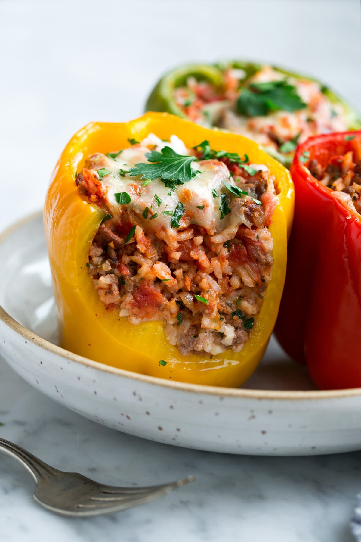 Stuffed Bell Peppers cut in half to show filling including ground beef, rice, tomato sauce and cheese.